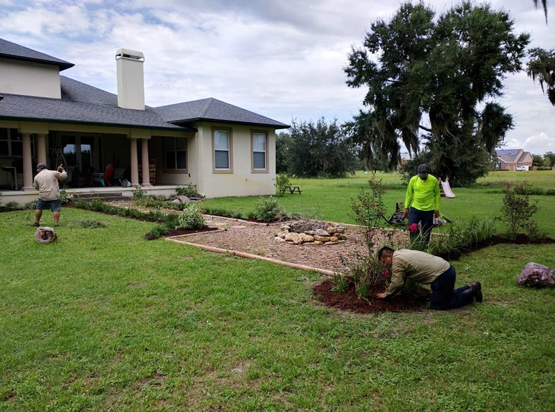Three Landscapers completing a custom fire pit install in Mount Dora, Florida.